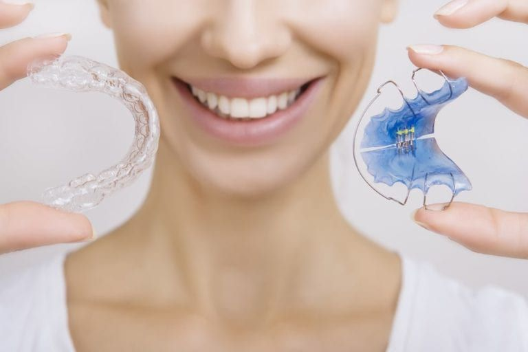 female girl with different types of retainers in hand