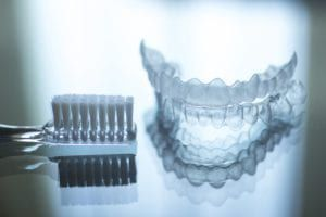Toothbrush beside a clear aligner