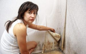 Woman peeling wallpaper to reveal black mold